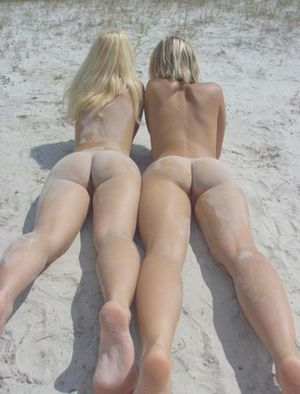 Two blonde girls posing on a beach..