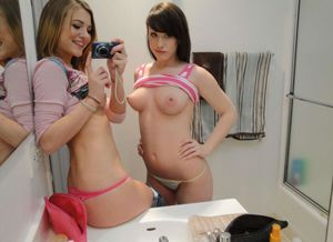 Two girls taking selfie showing their..