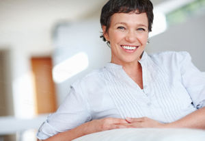 Smiling mature woman on couch Buy..