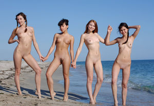Four pale dolls nude on the beach..