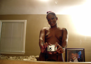 Tattoed young ebony taking pictures of..