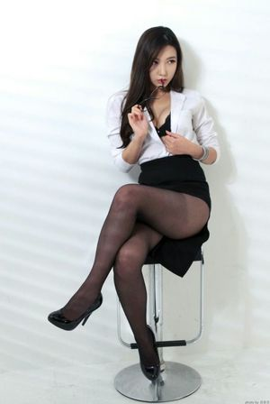 Asian girl crosses her pantyhose legs..