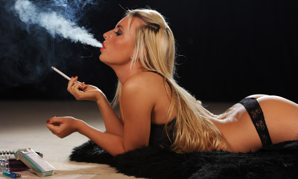 Sexy young blonde woman smoking cigarette in the parkclose up stock photo